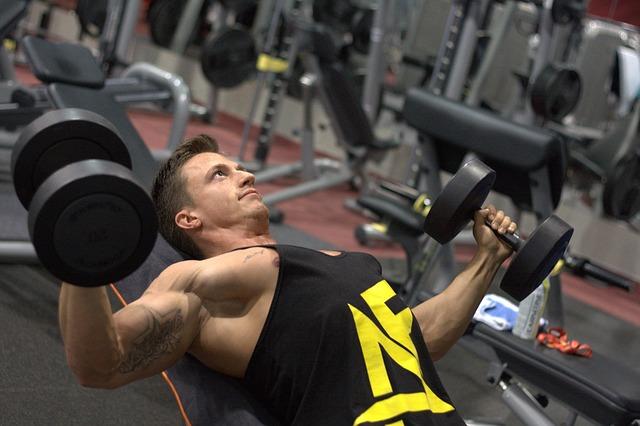 muž cvičící s činkami